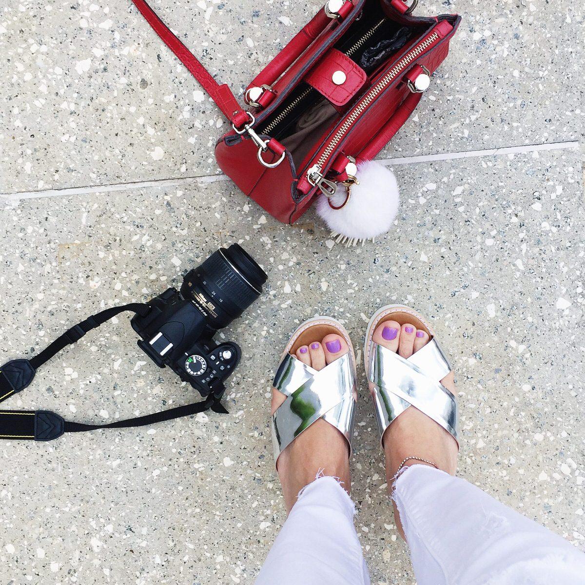 Camera fotografica Nikon, bolsa vermelha Schutz e sandália flatform prata Carrano